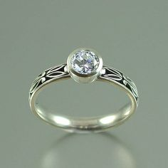 AUGUSTA 14K gold Moissanite engagement ring by WingedLion on Etsy, $780.00. Read the info on moissanite - it seems like a smart stone to use. This one has a matching wedding band (which you need to purchase separately).