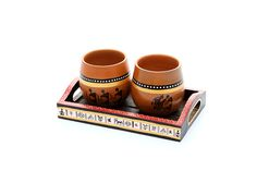 Warli hand painted set of 2 Chai Cups in clay.They are placed in a compact wooden tray which is again hand painted. These pair of cups and tray will add an ethnic look to your table decor.