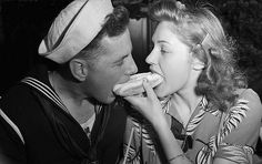 A sailor sharing a hot-dog with his girl. Coney Island, NY (1943)