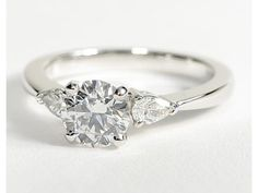Round solitaire engagement ring with pear-shaped diamonds