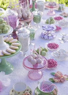 Afternoon tea (or cocktails) never looked so good: lace tablecloth, lots of glass, apothecary jars with candy, cake pops and French macarons in soft pinks, purples, and greens. #party