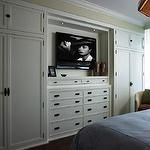 Bedroom built-ins with white built-in cabinets flanking white built-in dresser, TV and tan walls paint color.