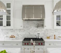Christine Donner Kitchens - kitchens - white kitchen, white kitchens, industrial pendants, industrial island pendants, industrial kitchen pendants, kitchen island, white kitchen island, white marble, white marble countertop, farmhouse sink, island sink, island farmhouse sink, barrel range hood, barrel kitchen hood, glass front kitchen cabinets, glass front upper cabinets, inset lower cabinets, marble subway tiles, integrated cooktop, integrated wolf cooktop,