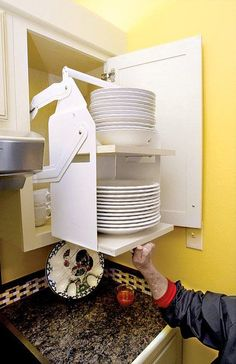 Pull-down shelves in an overhead cabinet are capable of holding heavy stacks of dishes.