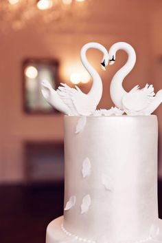 Handmade sugar swans perch on the lustre top tier of a luxury wedding cake