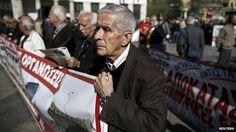 Pensioner holds banner during anti-austerity demonstration in Athens. 1 April 2015