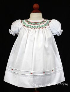 White smocked bishop dress with red & green hand-embroidered detailing around the neck and red flowers at the hem, pretty horizontal pleated detailing at the hem. So pretty!!