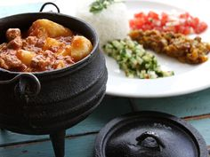 """Potjiekos - South Africa [It means """"small pot food."""" As a stew prepared outdoors, made in a 3-leg cast iron pot, the potjie descended from the Dutch oven of the Netherlands to South Africa in the 17th century and is now throughout the homes and villages of South Africa. The pot is heated using small amounts of wood or charcoal ]"""