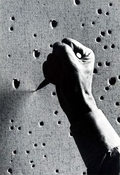 Textile texture, this must be Lucio Fontana working on one of his artworks.