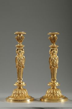 Pair of gilded and sculpted bronze candlesticks in Louis XVI style. Each stem is composed of three women facing outward supporting a vase, which is the socket, on their heads. The fluted vase is decorated with lion heads and rests on Griffin feet.