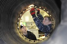 Aviation Machinist's Mate Airman Michael Walsh and Aviation Machinist's Mate Airman Chandra Tremayne perform maintenance on a 404-400 jet engine afterburner aboard the aircraft carrier USS Nimitz (CVN 68).
