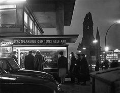 Simple Passanten stehen vor einer Vitrine zwischen dem DOB Hochhaus und dem Bahnhof Zoo In dem Schaukasten befindet sich ein Modell des Kreuzungsbahnhofs