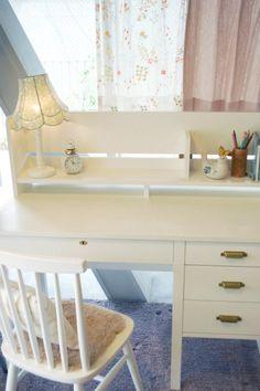ガーリーな白い机の奥に揺れるのは、小花柄カーテン。透ける素材が上品な感じ。