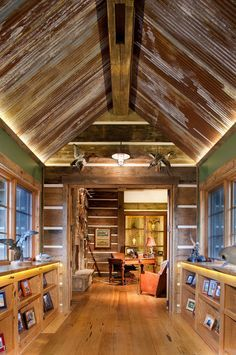 Check out the ceiling made from corrugated tin. The weathered and aged look complements the rustic feel of the stone house. Note the wood valance at the roof-wall junction: a clever solution that provides space for LED strip lighting.