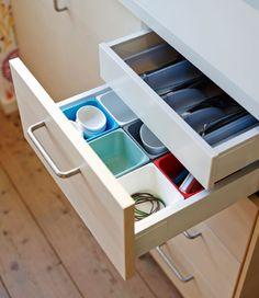 Offene Schublade mit VARIERA Behältern in verschiedenen Farben und versteckter Innenschublade für Besteck