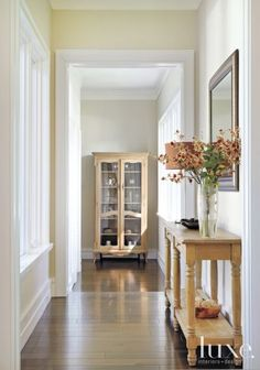 Crisp white millwork contrasts nicely with the hallway's rich, wide-planked walnut flooring from Deco27.