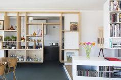 Een open, hangende wand scheidt de keuken gedeeltelijk af van de woonruimte.