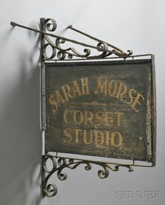 AMERICAN FURNITURE & DECORATIVE ARTS - SALE 2608M - LOT 1015 - PAINTED AND GILDED WOOD AND WROUGHT IRON SARAH MORSE CORSET STUDIO TRADE SIGN, AMERICA, LATE 19TH/EARLY 20TH CENTURY, DOUBLE-SIDED... - Skinner Inc