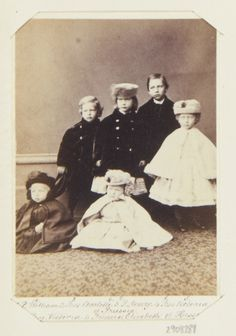 Carte-de-visite depicting a family group portrait. Standing left to right are Prince Henry of Prussia (1862-1929), Princess Charlotte of Prussia (1860-1919), Prince Wilhelm of Prussia (1859-1941), and their cousin Princess Victoria of Hesse and by Rhine (1863-1950). Princess Charlotte and Princess Victoria are both wearing hats. Seated in front of them are two younger children. Princess Elisabeth of Hesse and by Rhine (1864-1918)