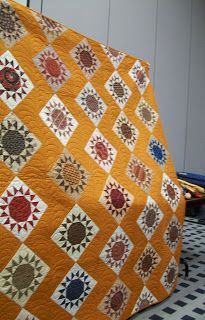 Wheel of Fortune, Sunburst?  I love the symmetry of the points around the snowball-circle.   Pieceful News: Pictures from Fall 2011 Quilt Market