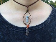 Handmade wire wrapped blue aura crystal quartz and carnelian adjustable necklace pendant, featuring a Hindu Hamsa Hand from CrystalAndVein on Etsy! https://www.etsy.com/listing/205862882/blue-quartz-point-wire-wrapped-necklace?ref=listing-shop-header-2 #hamsahand #hindu #blueauraquartz #blue #aura #crystal #quartz #wirewrapped #carnelian #leather #urban #hipster #adjustable #unique #jewelry #necklace #pendant #handmade