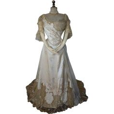 """two piece evening gown, cream brocade silk, tulle and lace, ca. 1898. Woven petersham: """"Worth, Paris"""". deaccessioned by The Museum of Early Southern Decorative Arts (MESDA Hand written notice: """"Evening Dress, Miss L.S. Drayer, worn about 1898"""". Front pleated bodice with tulle applications . Tulle applications. Sequins embroideries in the chest area. Back closure with laces. Over the lacing a closure with hooks and eyes. Skirt with silk floral boarder, lace and floral embroidered lace."""