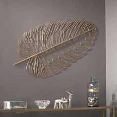 Feather your nest and quickly bring empty walls to life with the Aiden Lane Rahu Metal Feather Wall Sculpture. Metal wall sculpture blends into your curated décor collection or hangs alone as a statement piece.Our Gold Metal Feather Wall Plaque will