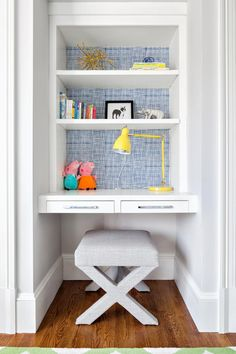 This built-in desk in a kid's bedroom gets a fun pop of color with bright wallpaper that's hung only on the backs of shelves. A modern upholstered stool and bright yellow desk lamp turn the small space into a functional study area.