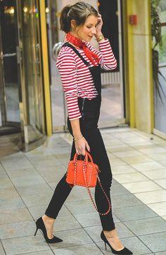 Street style look blusa listrada, macacão preto, bandana e bolsa vermelha.