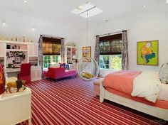 This Westchester kids room has a white sleigh bed with white and pink bedding, hot pink velvet seating, a globe seat hanging from a bar in the skylight, white and pink furniture and bright pink striped carpet.