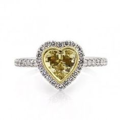 Yellow Heart Shape Diamond Engagement Ring - A mesmerizing Yellow Heart Shape Diamond Engagement Ring featuring a .55 carat Yellow Heart Shaped gemstone placed in a designer setting. This GIA certified ring is flanked with halo style White Round Brilliant cut accent stones on the shank. The center diamond is a Fancy Yellow in color, the accent stones are white, SI2 in clarity & stamped in 18k White Gold. The total gem weight is 1.35 carats & the diamonds are 100% natural…