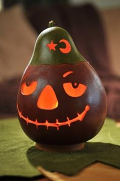 Burnt orange jack-o-lantern with a green lid.