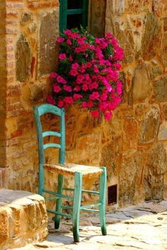 Beautiful flowers hanging from the windowsill and chair in Mallorca , Spain