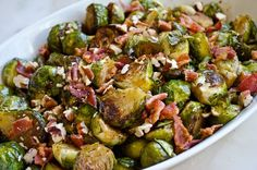 Roasted Brussels Sprouts with Bacon, Pecans & Maple Syrup - 1/2 cup pecans, 6 slices bacon, 2 pounds brussels sprouts, halved (stem and ragged outer leaves removed), 3 tablespoons extra virgin olive oil, 1 teaspoon kosher salt, 1/2 teaspoon freshly ground black pepper, 2-1/2 tablespoons balsamic vinegar, 1 tablespoon maple syrup.