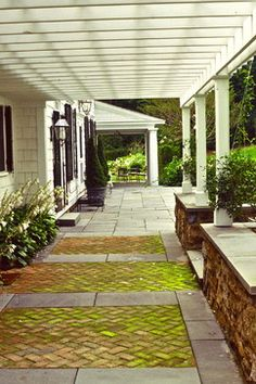 combination of brick and bluestone leading to the primary rear dinning space. The pergola
