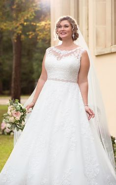 This traditional ball gown plus size wedding dress from Stella York features lace over tulle in a soft A-line silhouette, perfect for the classic bride! The voluminous skirt feels full and flowy while remaining light-as-air as layers of tulle are adorned with delicate lace details that give off a unique effect. The illusion lace neckline, that highlights the blushing bride's face, continues to the back of the ball gown where floral patterned lace creates a stunning back. Fabric covered…