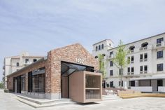 Beijing-based BLUE Architecture Studio has inserted a rectangular volume down the middle of an existing building in China to form a cafe that juxtaposes old and new. Exposed Aggregate Concrete, Concrete Floors, Axonometric View, R Cafe, Outdoor Seating Areas, Large Planters, Brick Building, Red Bricks, Cafe Interior