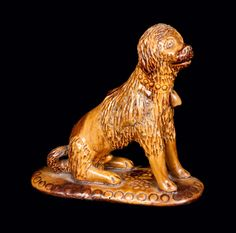 Price Realized: $ 460.00 Glazed Redware Figure of a Seated Dog, Pennsylvania origin, mid 19th century, hand-modeled and incised figure of a seated dog with poodle cut, curled tail, and well-detailed face and coat, the figure's neck with impressed collar and applied bell. Oval base with impressed circular border and impressed floral decoration below dog. Figure is hollow, and rattles with pieces of clay when shaken. Surface decorated with daubs of manganese