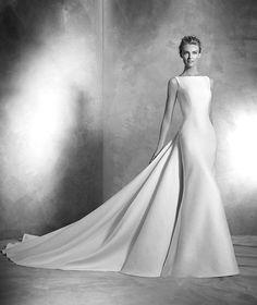 Venia, robe de mariée simple, décolleté bateau, style classique Robe de mariée simple en piqué, silhouette sirène. Décolleté bateau sur le devant et décolleté plongeant en V dans le dos. Traîne amovible avec nœud. A partir de 1390€