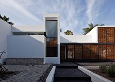 Atelier ARS° screens Mexican house behind stone wall and latticework.