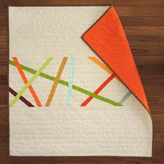 "Eggshell background with 10 different colored ""sticks"" in a free-for-all design.A Kumquat back and Sienna binding add a nice kick, too.30x30..."