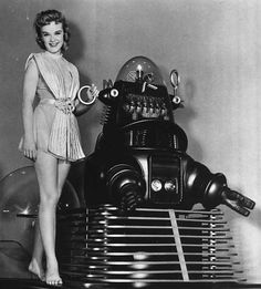 Anne Francis and Robby in Forbidden Planet. Forbidden Planet is a 1956 MGM science fiction film directed by Fred M. Wilcox, a screenplay by Cyril Hume, and starring Walter Pidgeon, Anne Francis, and Leslie Nielsen. Forbidden Planet is the first science fiction film in which humans are depicted traveling in a starship of their own creation. It was also the very first science fiction film set entirely on another world in interstellar space, far away from the planet Earth Fiction Film, Science Fiction, Walter Pidgeon, Leslie Nielsen, Anne Francis, Classic Sci Fi, Interstellar, Another World, Far Away