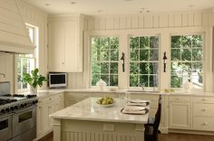 Antique white shaker kitchen cabinets with marble. vertical planking on walls, windows