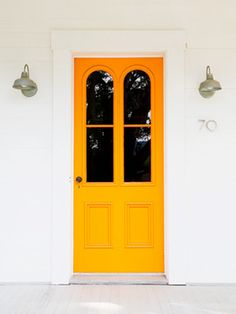 Yellow orange front door on white house with pretty wall sconces