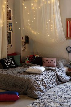 bed on floor, hanging lights and fabric