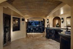 Custom home bar in luxury basement with dark cabinets