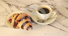 A croissant and a cup of coffee