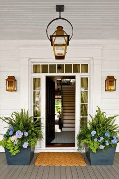 Love the blue hydrangeas in the black pots, the straw mat and the brass accents.