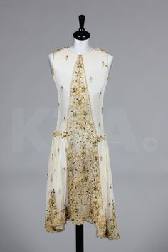 An ivory tulle and beetle-wing adorned dress, circa 1926, probably formed from an Edwardian skirt panel, further embellished with gold embroidery.