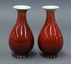 "Two Chinese Langyao Porcelain Bottle Vases with a trumpet neck and a pear shaped body, thining grey at the rim and red on the body, raised on a splayed foot, 6.75""h"
